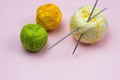 Produkter för handarbete som sticker Bollar av gult, grönt purpurfärgat garn, stickor på en rosa bakgrund royaltyfria foton