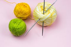 Produkter för handarbete som sticker Bollar av gult, grönt purpurfärgat garn, stickor på en rosa bakgrund arkivbilder