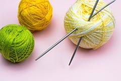 Produkter för handarbete som sticker Bollar av gult, grönt purpurfärgat garn, stickor på en rosa bakgrund arkivfoton