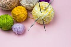 Produkter för handarbete som sticker Bollar av gult, grönt purpurfärgat garn, stickor på en rosa bakgrund royaltyfri bild