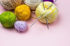 Produkter för handarbete som sticker Bollar av gult, grönt purpurfärgat garn, stickor på en rosa bakgrund royaltyfria bilder