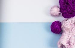 Produkter för handarbete som sticker Bollar av rosa purpurfärgat garn på en blå bakgrund arkivfoton