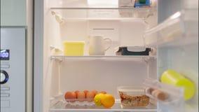 Produkter och mat visas och fyller kylen inomhus arkivfilmer