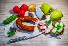 """Produkter på tabellâ€en """"rökte korven, brunt bröd, ost och grönsaker royaltyfria bilder"""