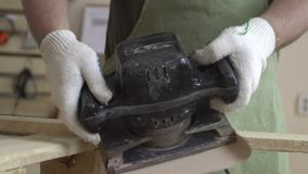 Produkter som göras av naturligt trä och arbete på dem Arbete med trästrukturer och den malande maskinen Förlage i vita handskar arkivfilmer