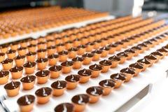 Produktion av brända mandlar i en fabrik för livsmedelsindustrin - automatisk royaltyfri foto