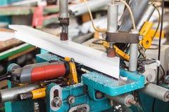 Produktion av PVC-fönster, en maskin för framställning av hål i den plast- profilen av PVC-fönstret, drillborr royaltyfria bilder
