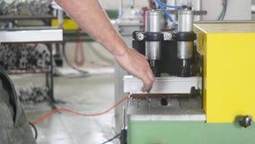 Produktion av pvc-fönster, mannen installerar en pvc-profil i den bitande maskinen och klipper den för att passa för ytterligare  lager videofilmer