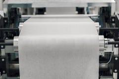 Produktion på den pappers- rullmaskinen arkivbild