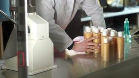 Produktion von Kosmetik Laborweibliches Assistenzwegnehmen Flaschen Shampoo und sie tragen stock footage