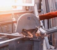 Produktion von PVC-Fenstern, Arbeitskraft schneidet ein Metallprofil auf einer Kreissäge, Nahaufnahme, Hand, Sonne stockfotos