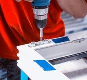Produktion von PVC-Fenstern, die Arbeitskraft wird mit einem Schraubenzieher mit einem Verschluss zum PVC-Fenster, Nahaufnahme, S Stockfotografie