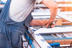 Produktion von PVC-Fenstern, ein Mann schraubt einen Schraubenzieher in ein PVC-Fenster, Nahaufnahme, Fenster-PVC lizenzfreie stockbilder