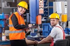 Produktionsarbeitskraft am Arbeitsplatz und Aufsichtskraft stockbilder