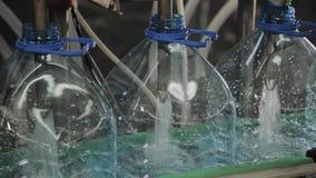 Produktionslinje av dricksvatten och kolsyrade drinkar, processen av att fylla flaskor med vatten, transportör arkivfilmer