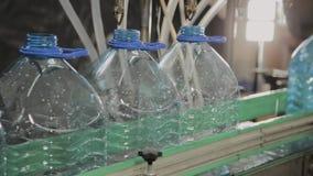 Produktionslinje av dricksvatten och kolsyrade drinkar, processen av att fylla flaskor med vatten, transportör lager videofilmer