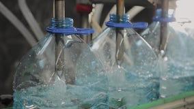 Produktionslinje av dricksvatten och kolsyrade drinkar, processen av att fylla flaskor med vatten, transportör stock video