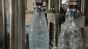 Produktionslinje av dricksvatten och kolsyrade drinkar, processen av att fylla flaskor med vatten, transport?r arkivfilmer