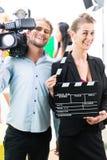 Produktionsteam mit Kamera und Nehmen klatscht auf Filmkulisse oder Studio Lizenzfreie Stockbilder