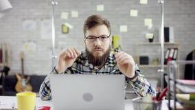 Produktiv allvarlig strävsam affärsman som lutar avslutande tillbaka kontorsarbete på bärbara datorn, tillfredsställd effektiv ch arkivfilmer