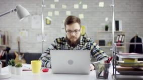 Produktiv metodisk affärsman som lutar avslutande tillbaka kontorsarbete på bärbara datorn, effektiv chef som tillfredsställs med lager videofilmer
