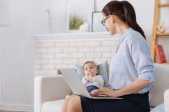 Produktive Geschäftsdame, die ihr Kind beachtet Lizenzfreie Stockfotografie