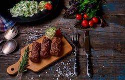 Produktu grill: stek, kiełbasa i warzywo na nieociosanym drewnianym stole, Kiełbasy na grill niecce na drewnianym tle horyzont Zdjęcie Stock