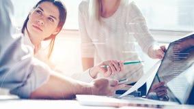 Produktuntersuchung Marketing-Team bei der Arbeit Dachbodenbüro Laptop und Schreibarbeit Statistikdiagrammüberlagerung, Ikoneninn stockfotografie