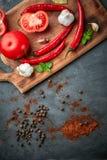 Produktuppsättning med tomater, chilipeppar, vitlök och kryddor på träcatboard på den mörka stentabellen arkivfoto