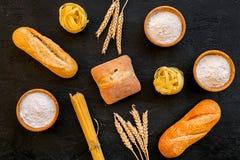Produkty robić pszeniczna mąka Biała mąka w pucharze, pszenicznych ucho, świeżym chlebie i surowym makaronie na czarnego tła odgó fotografia royalty free