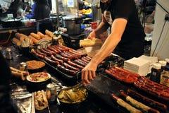 Produrre gli hot dog in Bricklane ad un mercato di Londra Fotografia Stock