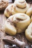 Produrre i panini di cannella Pasta di lievito casalinga dopo l'innalzamento Immagine Stock