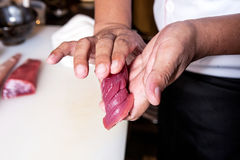 Produrre i sushi del pesce crudo a mano Fotografia Stock
