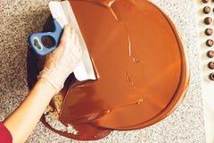 Produrre il cioccolato fatto a mano Il confettiere versa il cioccolato fondente liquido alla superficie Primo piano Fuoco seletti immagini stock libere da diritti