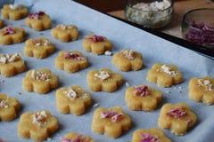 Produrre le pasticcerie dei biscotti del cece con le mandorle ed il tè è aumentato petali Dolci orientali tradizionali Il glutine fotografie stock