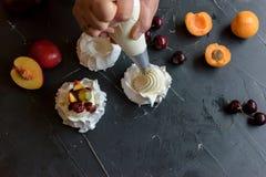 Produrre un dessert di Pavlova con frutta ed inceppamento Fotografia Stock