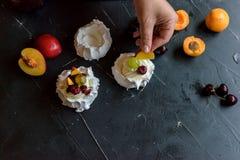 Produrre un dessert di Pavlova con frutta ed inceppamento Immagini Stock Libere da Diritti