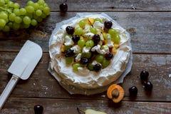 Produrre un dessert di Pavlova con frutta ed inceppamento Immagine Stock