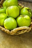 Produto local das bio maçãs orgânicas maduras verdes em vagabundos do vime do vintage Fotos de Stock