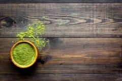 Produto tradicional japonês Chá verde de Matcha na bacia e dispersado no espaço de madeira escuro da cópia da opinião superior do imagem de stock royalty free