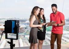 Produtor de televisão que fala com os apresentadores fêmeas sobre o programa televisivo imagem de stock royalty free
