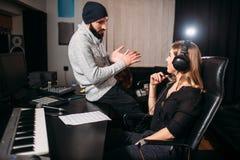 Produtor sadio com o cantor fêmea no estúdio da música imagens de stock