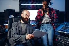 Produtor sadio masculino e cantor fêmea no estúdio foto de stock