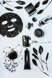 Produtos cosméticos faciais da beleza com carvão vegetal ativado: pó, máscara principal preta, máscara da folha e acessórios das  imagem de stock