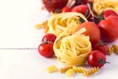 Produtos da massa com do alimento italiano cru dos ingredientes do Fettuccine de Fusili da massa do queijo do tomate fim branco d fotos de stock royalty free