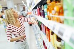 Produtos de compra do cuidado do corpo da mulher bonita fotos de stock