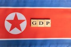 Produtos internos ou GDP bruto da Coreia do Norte em letras de bloco de madeira na bandeira norte-coreana foto de stock royalty free