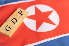 Produtos internos ou GDP bruto da Coreia do Norte em letras de bloco de madeira na bandeira norte-coreana imagens de stock royalty free