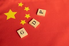 Produtos internos ou GDP bruto de China em letras de bloco de madeira na bandeira chinesa imagens de stock royalty free