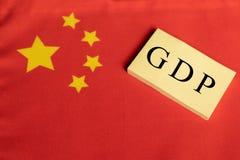 Produtos internos ou GDP bruto de China em letras de bloco de madeira na bandeira chinesa foto de stock royalty free